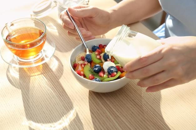 Frau, die leckeren joghurt auf früchte in schüssel am tisch gießt
