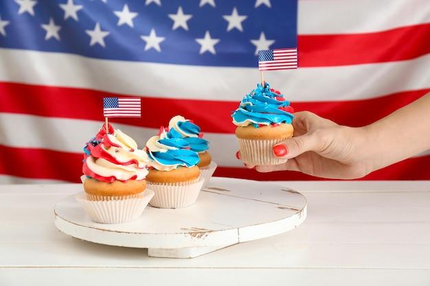 Frau, die leckeren patriotischen cupcake vom tisch nimmt