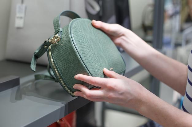 Frau, die ledertasche am shop wählt