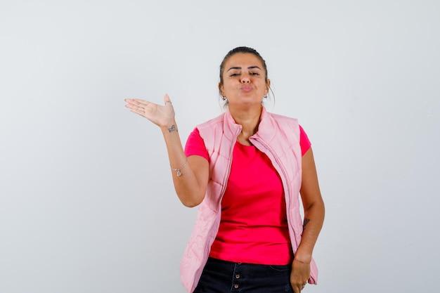 Frau, die leere handfläche zeigt, während sie die lippen in t-shirt, weste schmollen und süß aussieht