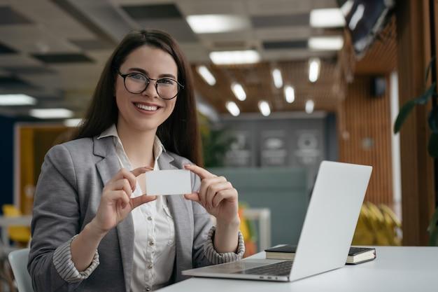Frau, die leere visitenkarte mit kopienraum hält, im modernen büro sitzt