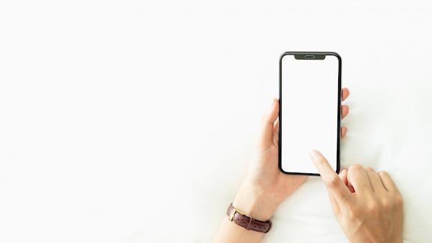 Frau, die leeren bildschirm von smartphone auf raum, während der freizeit verwendet.