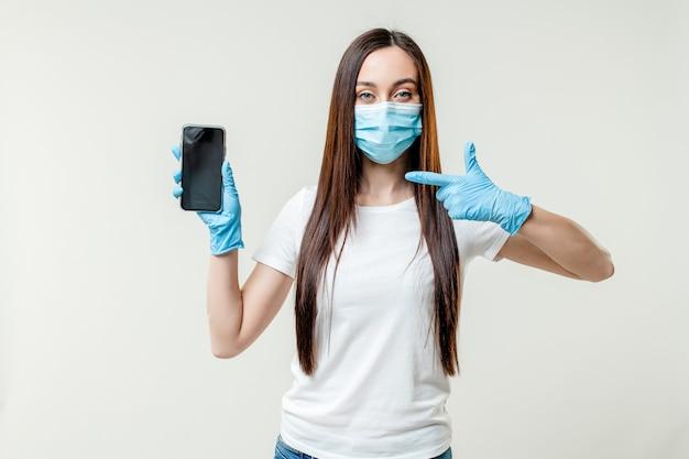 Frau, die leeren bildschirmraum-telefonbildschirm trägt maske und handschuhe zeigt