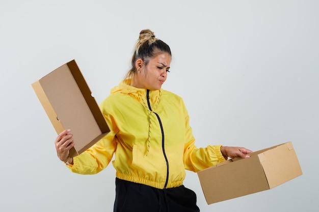 Frau, die leeren karton im sportanzug hält und enttäuscht schaut. vorderansicht.