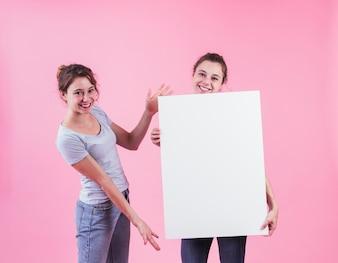 Frau, die leeren Plakatgriff von ihrem Freund gegen rosa Hintergrund darstellt