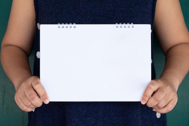 Frau, die leeren weißen kalender zeigt