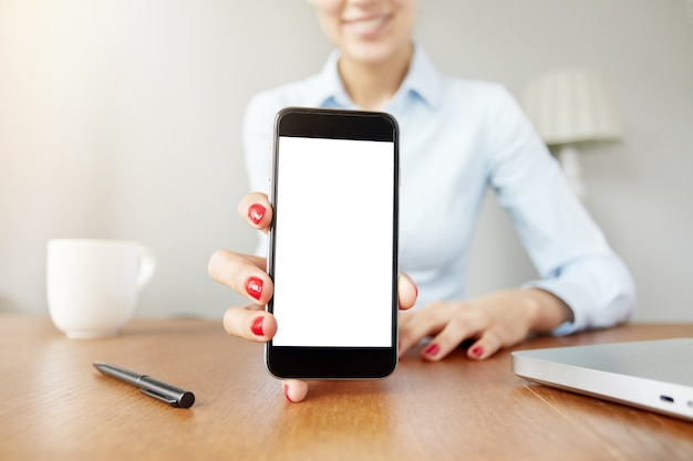 Frau, die leeren weißen smartphonebildschirm hält
