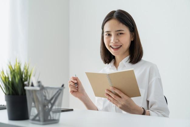 Frau, die leeres notizbuch und stift auf tabelle im büro hält.