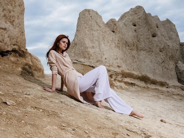 Frau, die leichte kleidung auf dem sand nahe den felsen und hohen steinen trägt