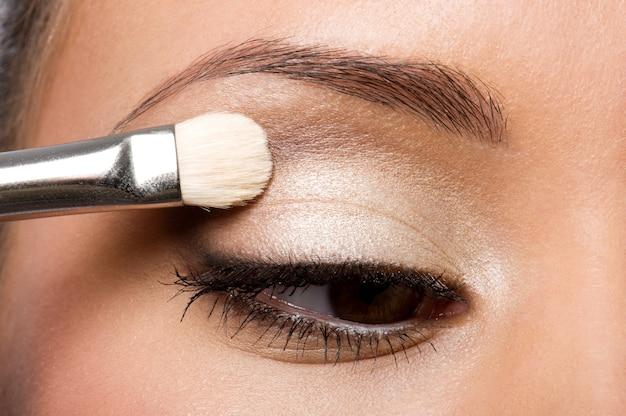 Frau, die lidschatten auf augenlid unter verwendung des make-up-pinsels anwendet