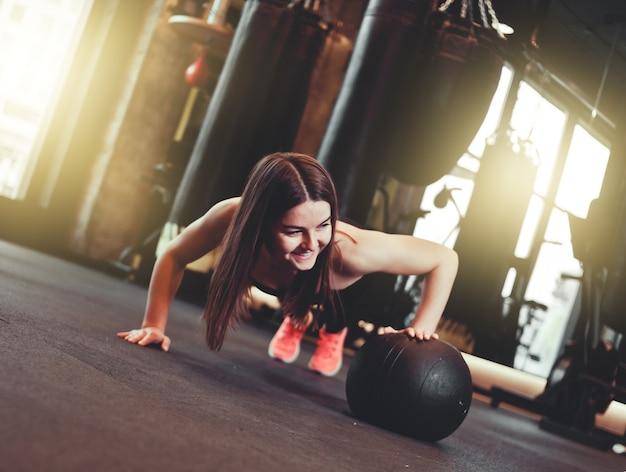 Frau, die liegestütze mit medizinball im dunklen fitnessstudio tut