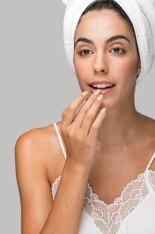 Frau, die lippenbalsam anwendet