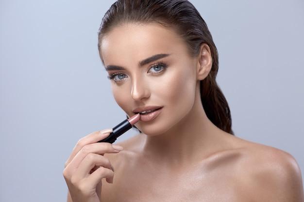 Frau, die lippenstift anwendet und in die kamera schaut, mädchen mit lippenstift, hübsche brünette, die lippenstift anwendet, schönes mädchen, das make-up anwendet