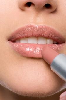 Frau, die lippenstift auf lippen anwendet - nahaufnahme