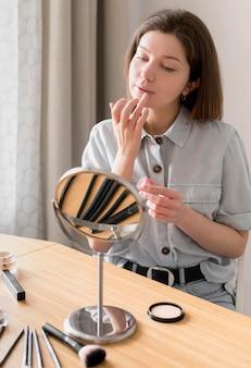 Frau, die lippenstift mit der hand anwendet
