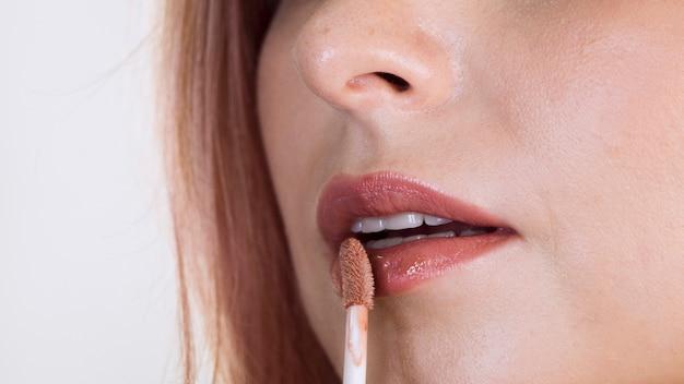 Frau, die lippenstiftprodukt anwendet
