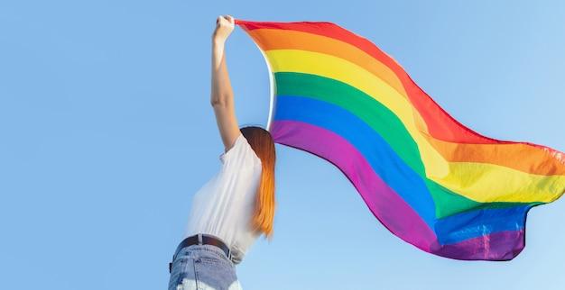 Frau, die lisbian regenbogen lgbt flagge über blauem himmel im freien hält. glücksfreiheit und liebeskonzept für gleichgeschlechtliche paare.
