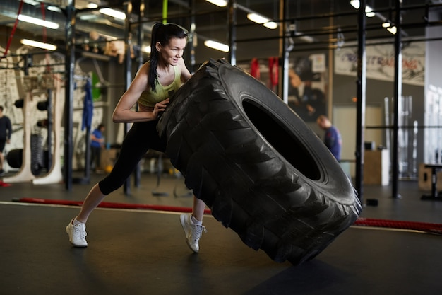 Frau, die lkw-reifen im fitnessstudio umdreht