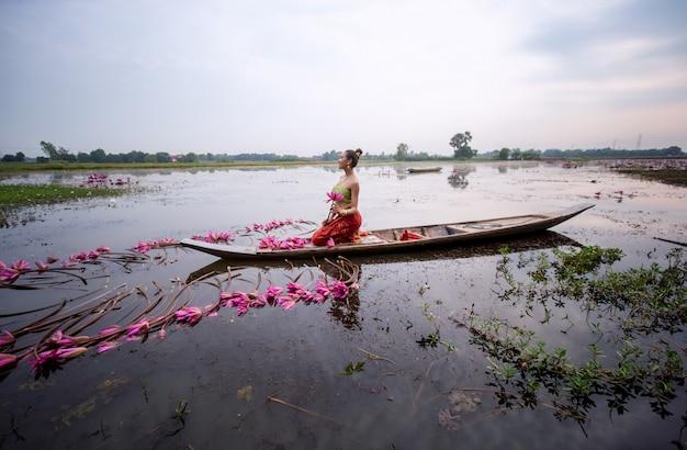 Frau, die lotus beim sitzen auf boot im see hält