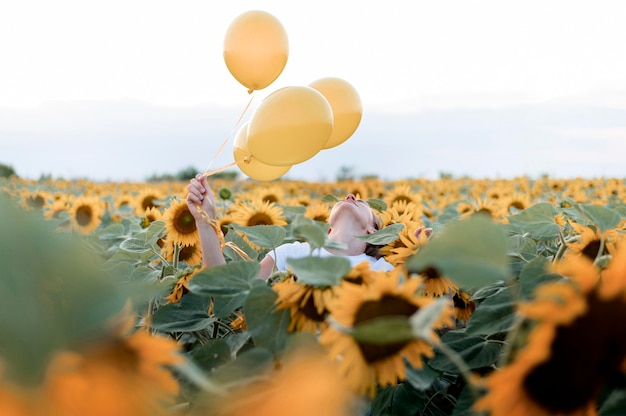Frau, die luftballons im sonnenblumenfeld hält