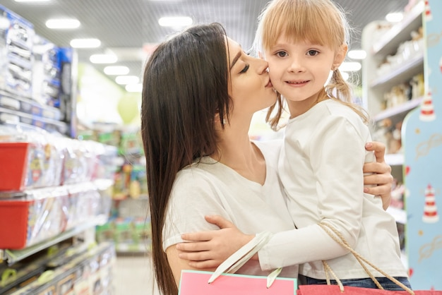Frau, die mädchen umarmt und im einkaufszentrum küsst.