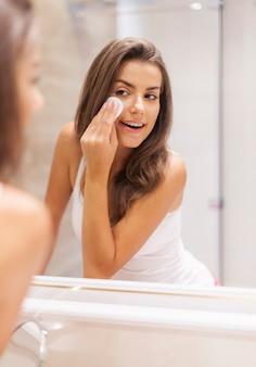 Frau, die make-up von ihrem gesicht entfernt