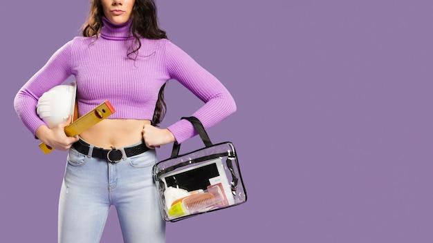 Frau, die make-upausrüstung und bausatzkopienraum hält