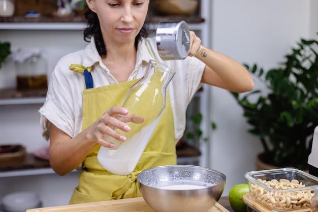 Frau, die mandelmilch in glasflasche gießt