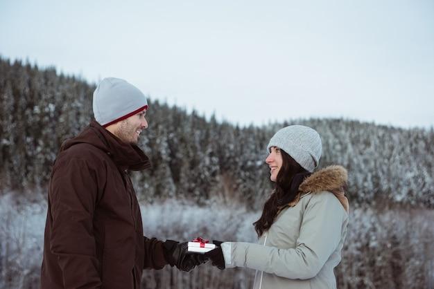 Frau, die mann auf schneebedecktem berg geschenk gibt