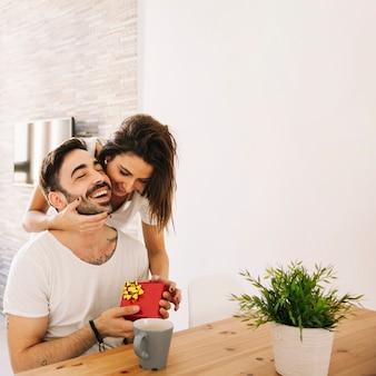 Frau, die mann beim geben des geschenkes umarmt