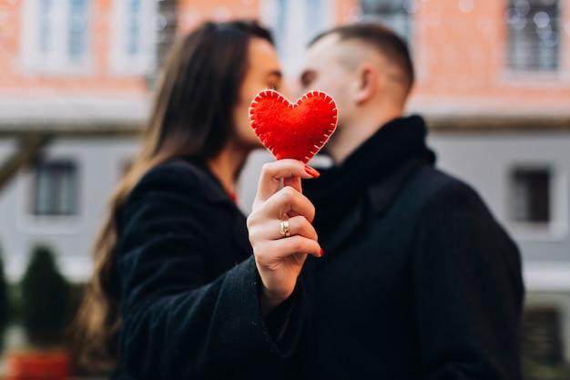 Frau, die mann beim zeigen des roten herzens küsst