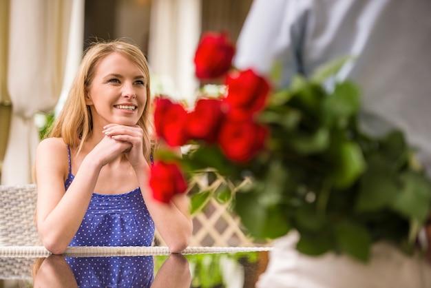 Frau, die mann mit blumenblumenstrauß hinter der rückseite betrachtet.