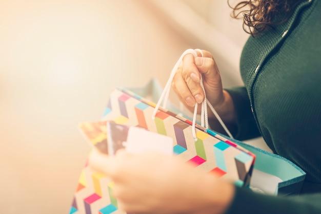 Frau, die marke auf einkaufstasche betrachtet