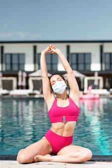 Frau, die maske am pool trägt