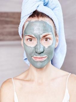 Frau, die maske befeuchtende hautcreme auf gesicht schaut, das im badezimmerspiegel schaut. mädchen, das sich um ihren teint kümmert, der feuchtigkeitscreme überlagert. hautpflege spa-behandlung.
