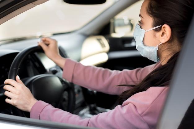 Frau, die maske in ihrem eigenen auto trägt