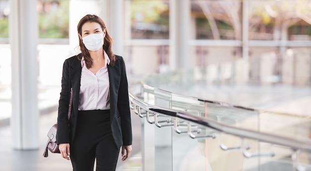 Frau, die maske trägt, die in stadt geht