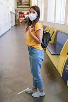 Frau, die maske trägt und auf öffentliche verkehrsmittel wartet