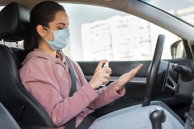 Frau, die maske trägt und händedesinfektionsmittel verwendet