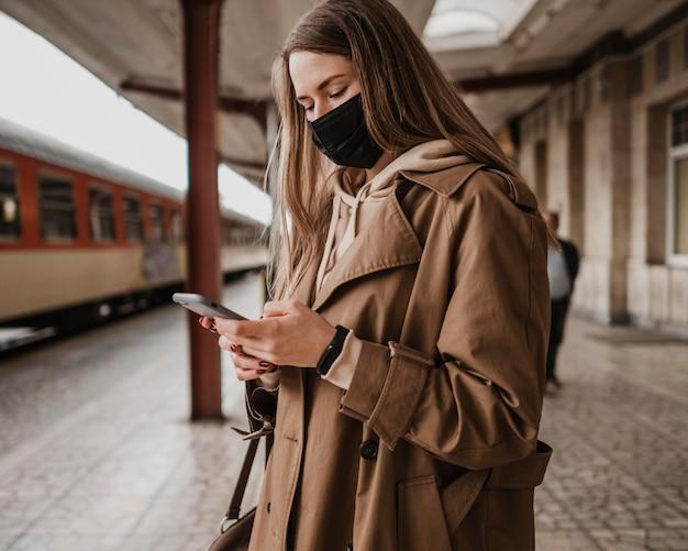 Frau, die maske trägt und handy im bahnhof verwendet