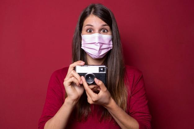 Frau, die maske trägt und kamera hält