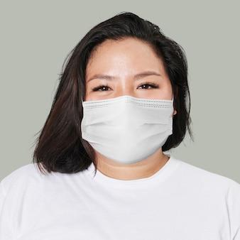 Frau, die maskengesichtsnahaufnahme covid-19 auf grünem hintergrund trägt