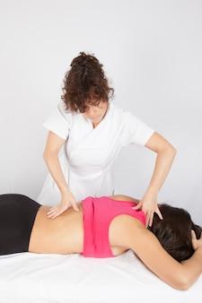 Frau, die massage auf schultern in der sportklinik empfängt