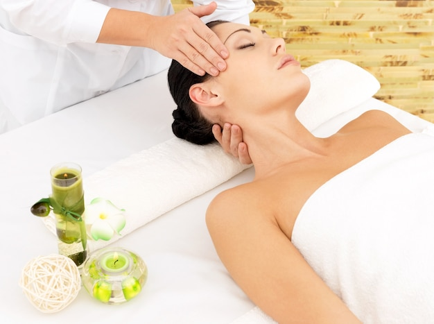 Frau, die massage des gesichts im spa-salon hat. schönheitsbehandlungskonzept.