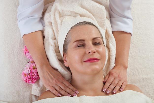 Frau, die massage für gesicht und hals im spa-salon bekommt