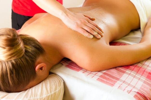 Frau, die massage im wellnessbadekurort genießt