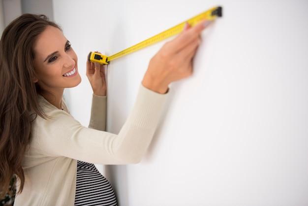 Frau, die maßnahmen im zukünftigen wohnzimmer ergreift