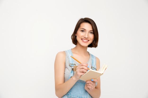 Frau, die maßnahmen während der hausrenovierung aufschreibt