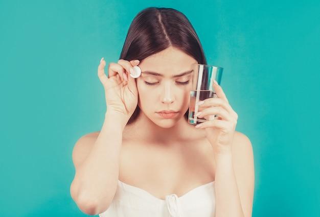 Frau, die medikamente nimmt, um kopfschmerzen zu lindern. brunette nimmt einige pillen, hält ein glas wasser, isoliert auf blau.