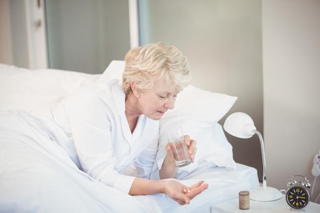 Frau, die medizin beim stillstehen auf bett einnimmt